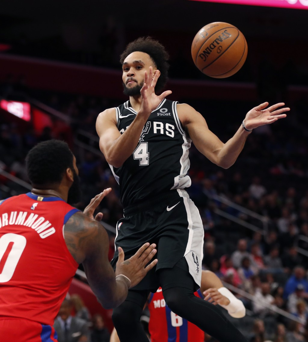 San Antonio Spurs guard Derrick White (4) passes in front of Detroit Pistons center Andre Drummond (0) during the first half of an NBA basketball game...