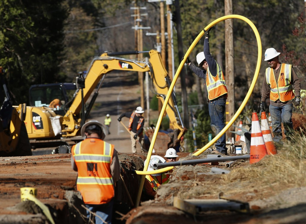 FILE - In this Oct. 18, 2019, file photo, Pacific Gas and Electric Company, workers bury utility lines in Paradise, Calif. A new technology being test...