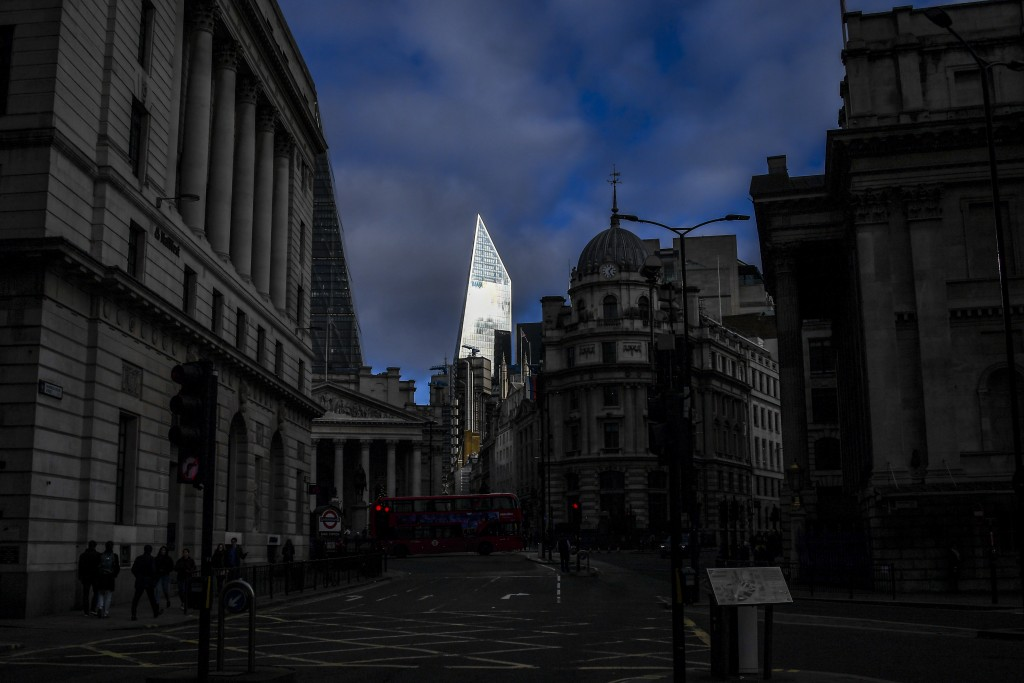 The sun reflects off a building in the City of London, near to London Bridge in London Sunday, Dec. 1, 2019.  A man wearing a fake suicide vest was su...