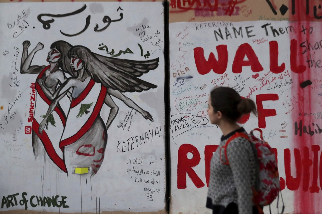 """In this Tuesday, Nov. 26, 2019 photo, a woman looks at a wall at United Nations Headquarters, decorated with graffiti in Arabic that reads, """"Revolutio..."""
