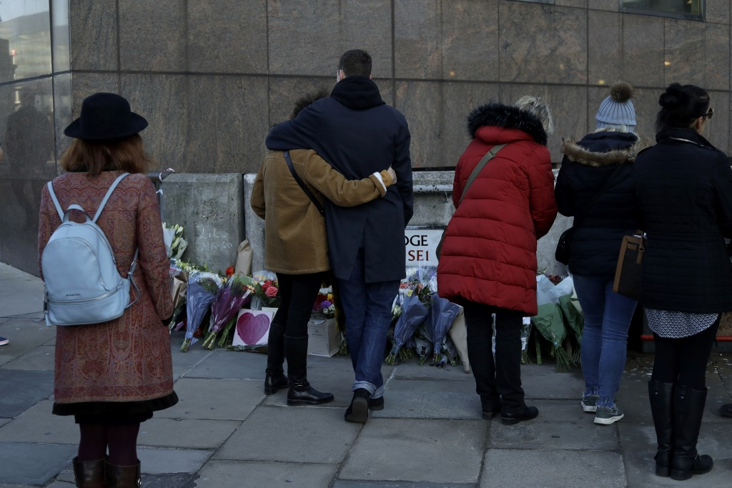 People look at flowers by London Bridge in London, after an earlier vigil outside the Guildhall, Monday, Dec. 2, 2019. London Bridge reopened to cars ...
