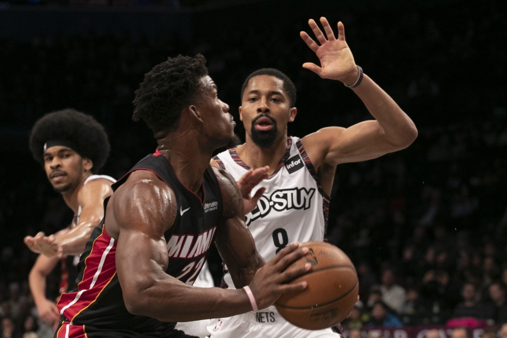 Miami Heat forward Jimmy Butler (22), left, drives against Brooklyn Nets guard Spencer Dinwiddie (8) in the first half of an NBA basketball game, Sund...