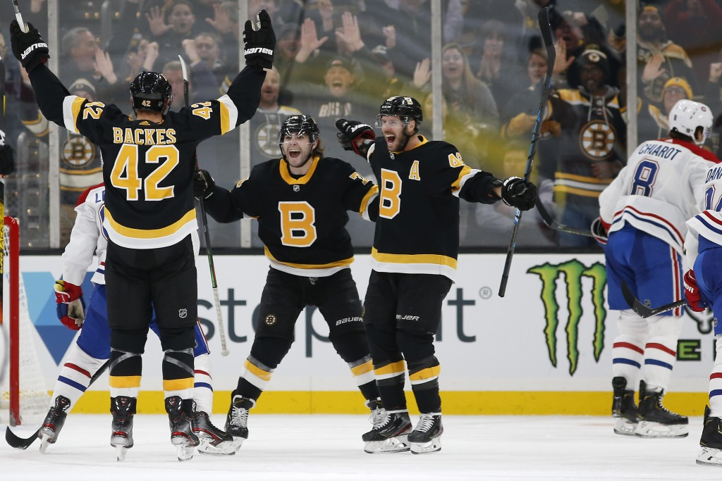 Boston Bruins' David Backes (42) celebrates his goal with David Krejci and Jake DeBrusk as Montreal Canadiens' Ben Chiarot skates away during the thir...