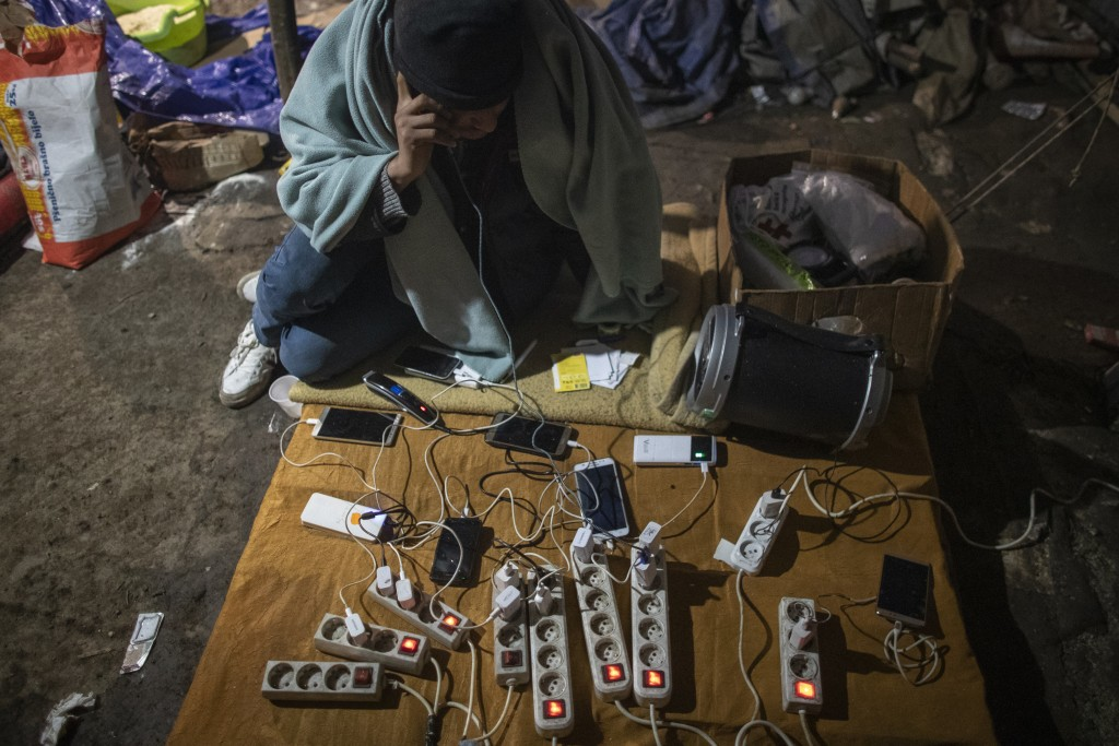 A migrant uses a mobile phone at a charging station at the Vucjak refugee camp outside Bihac, northwestern Bosnia, Sunday, Dec. 1, 2019. Despite the a...