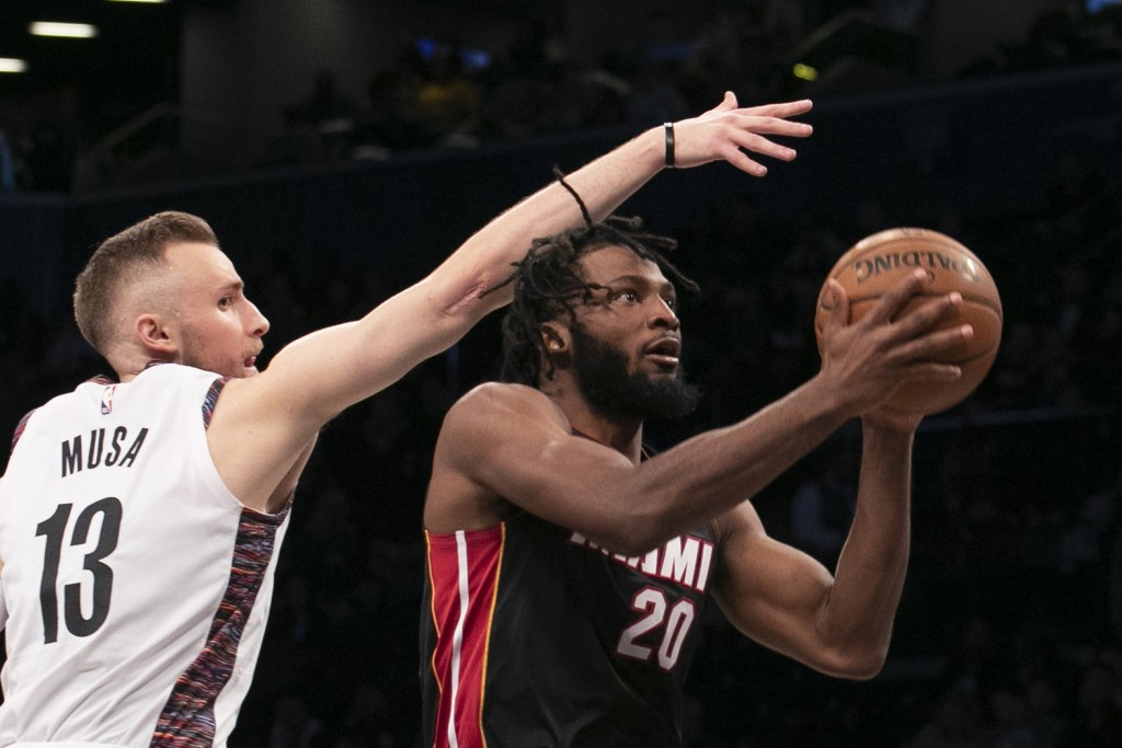 Brooklyn Nets guard Dzanan Musa (13) tries to block a shot by Miami Heat forward Justise Winslow (20) in the first half of an NBA basketball game, Sun...
