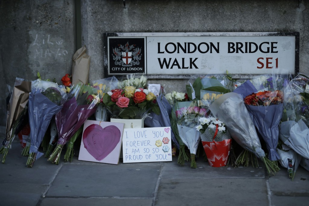 Tributes are placed by the southern end of London Bridge in London, Monday, Dec. 2, 2019. London Bridge reopened to cars and pedestrians Monday, three...