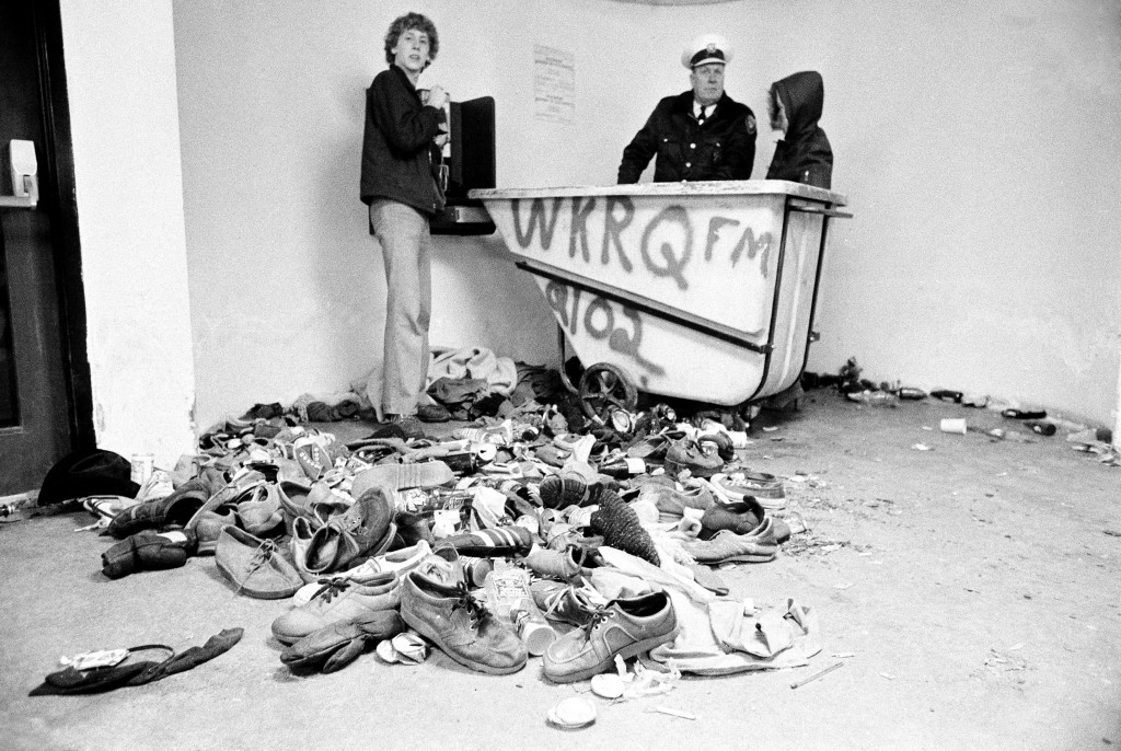 FILE - In this Dec. 3, 1979 file photo, concert-goers and a policeman stand with a pile of shoes and clothing which were left after a crowd surged tow...
