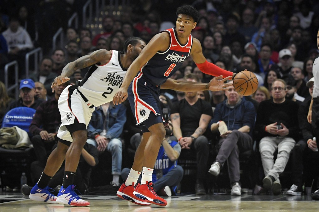 Los Angeles Clippers forward Kawhi Leonard, left, reaches in on Washington Wizards forward Rui Hachimura, of Japan, during the first half of an NBA ba...