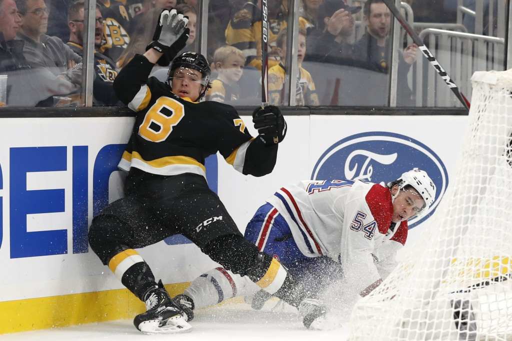 Montreal Canadiens' Charles Hudon, right, collides with Boston Bruins' Charlie McAvoy during the first period of an NHL hockey game Sunday, Dec. 1, 20...
