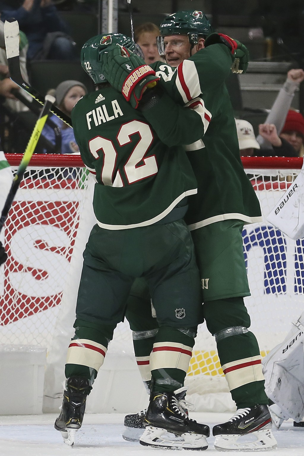 Minnesota Wild's Kevin Fiala hugs teammate Mikko Koivu in celebration after Fiala scored a goal against Dallas in the second period of an NHL hockey g...