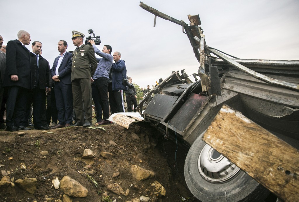 Tunisian President Kais Saied, left, talks with officials next to debris of a regional bus that crashed off a hill are pictured Sunday Dec.1, 2019, ca...