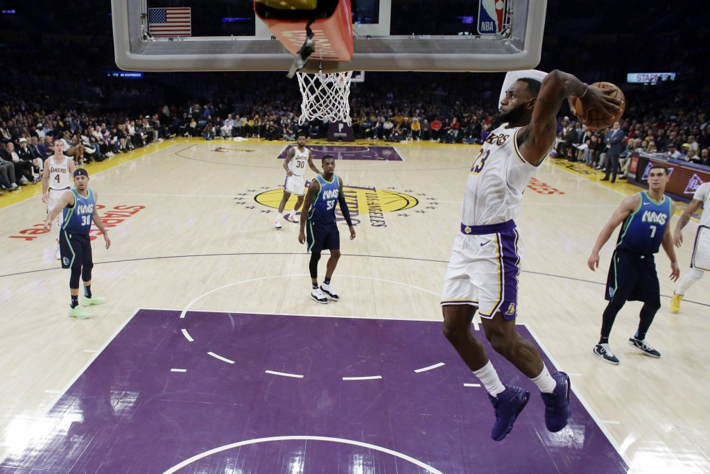 Los Angeles Lakers' LeBron James, right, dunks against the Dallas Mavericks during the second half of an NBA basketball game Sunday, Dec. 1, 2019, in ...