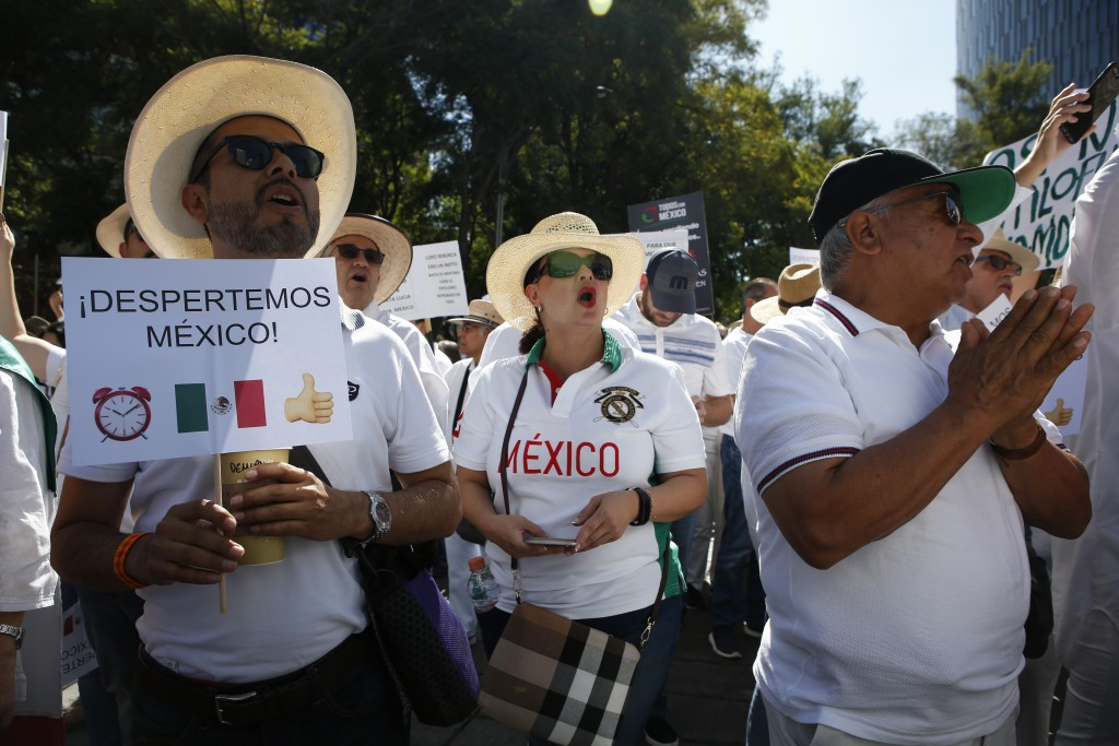 """A man holds a sign the reads in Spanish """"Mexico Wake Up!"""" as protesters shout out in support of the LeBaron family during a protest against the first ..."""