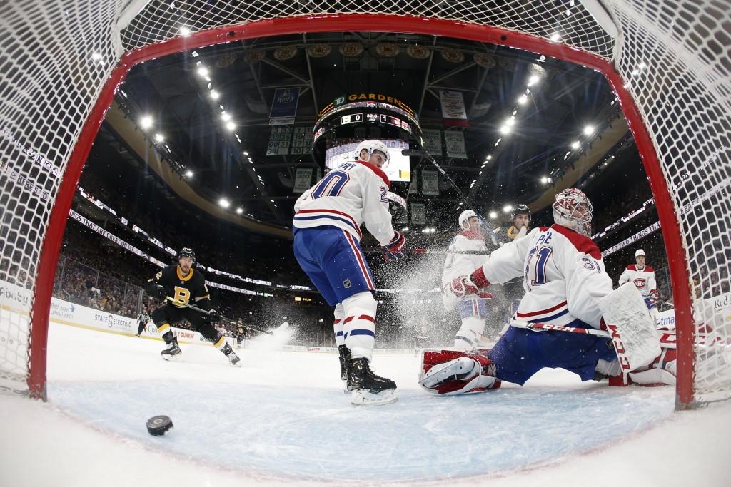 In this photo taken with a wide angle lens, Montreal Canadiens goaltender Carey Price looks behind him as the puck goes across the crease but not in a...