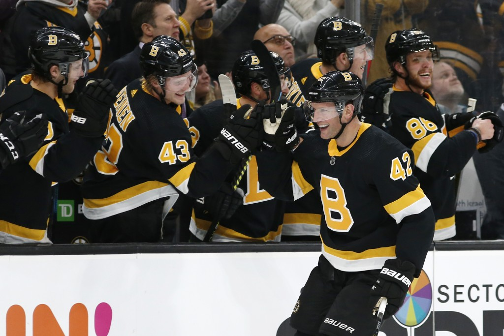 Boston Bruins' David Backes is congratulated by teammates at the bench after scoring against the Montreal Canadiens during the third period of an NHL ...