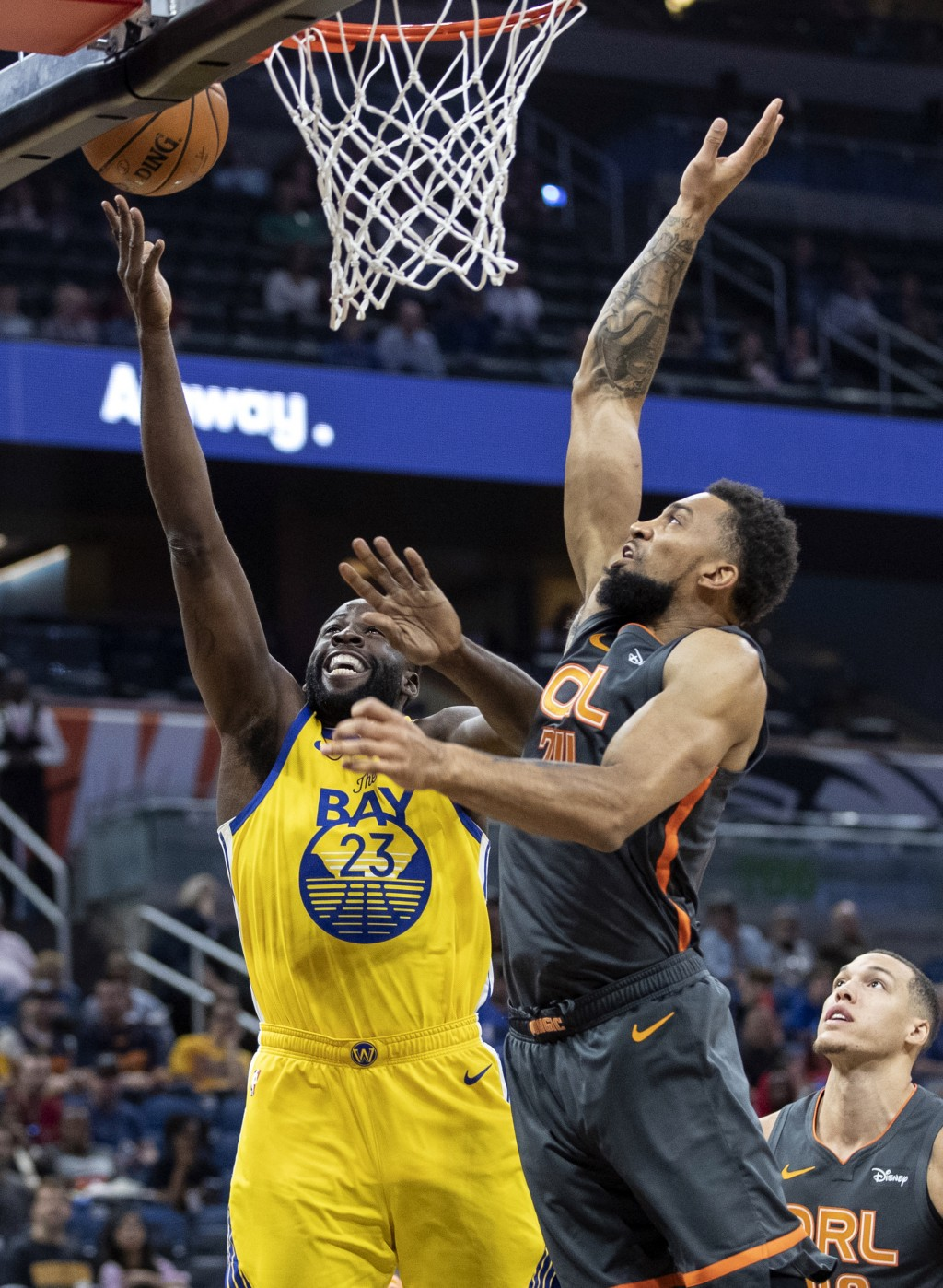 Golden State Warriors forward Draymond Green (23) lays the ball up on Orlando Magic center Khem Birch (24) during the first half of an NBA basketball ...
