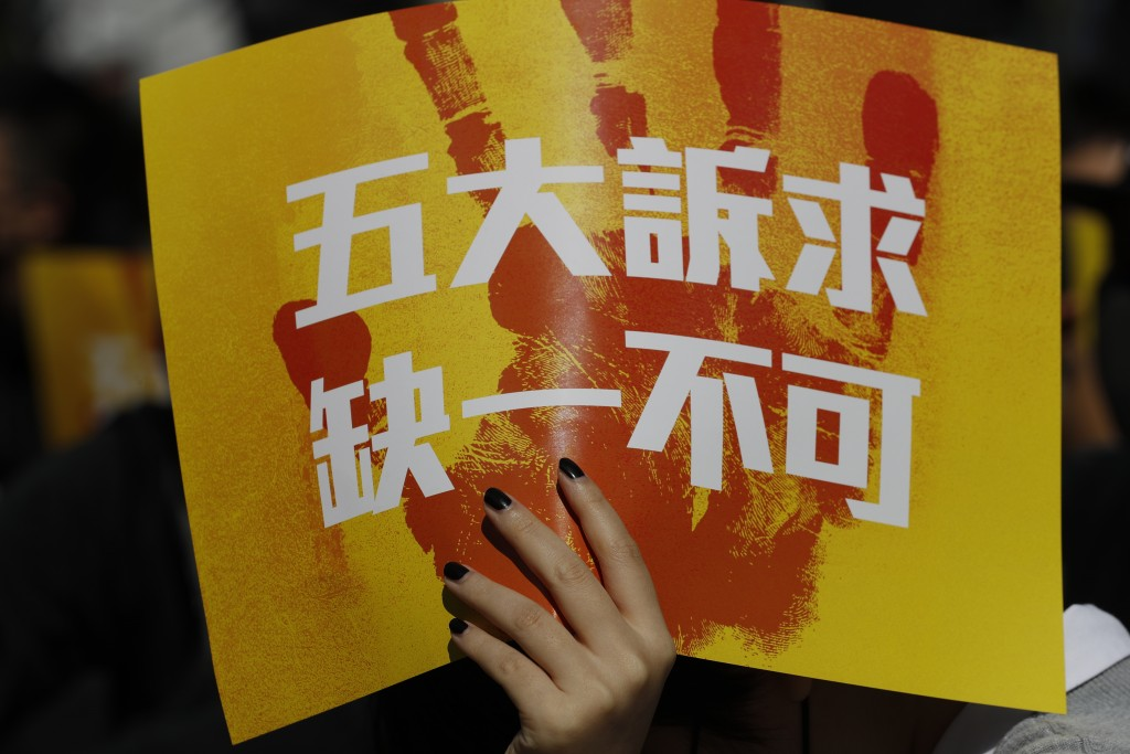 """A pro-democracy supporter holds up a card which reads """"Five Demands, Not one less"""" during a rally by the advertising industry in Hong Kong on Monday, ..."""