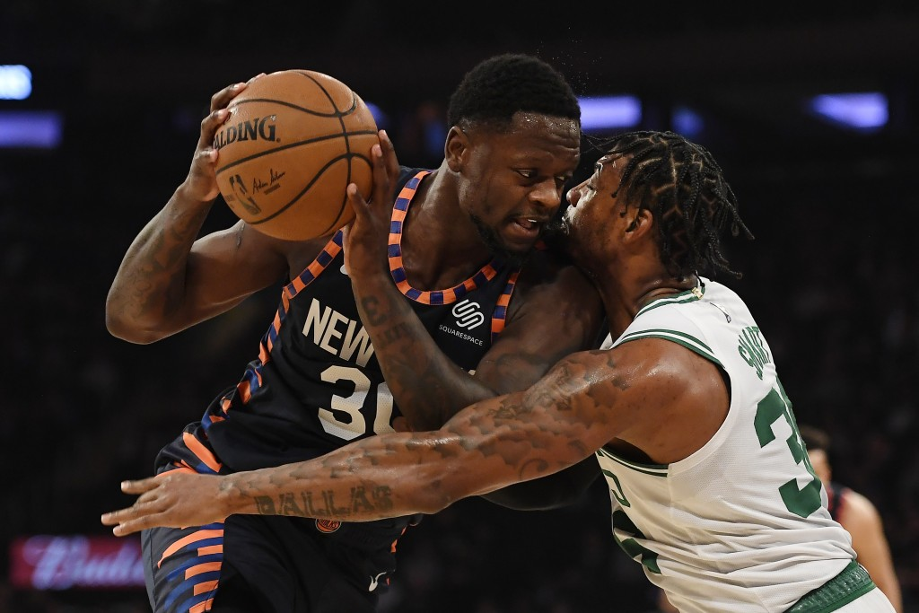 Boston Celtics guard Marcus Smart (36) reaches in against New York Knicks forward Julius Randle (30) during the first half of an NBA basketball game, ...