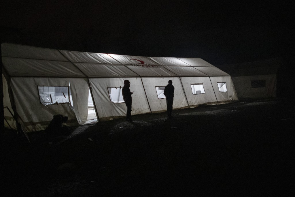 Migrants stand outside the mosque tent at the Vucjak refugee camp outside Bihac, northwestern Bosnia, Sunday, Dec. 1, 2019. Despite the approach of ha...