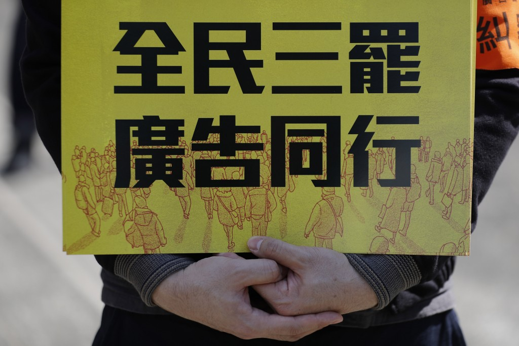 An anti-government supporter holds up a card which reads