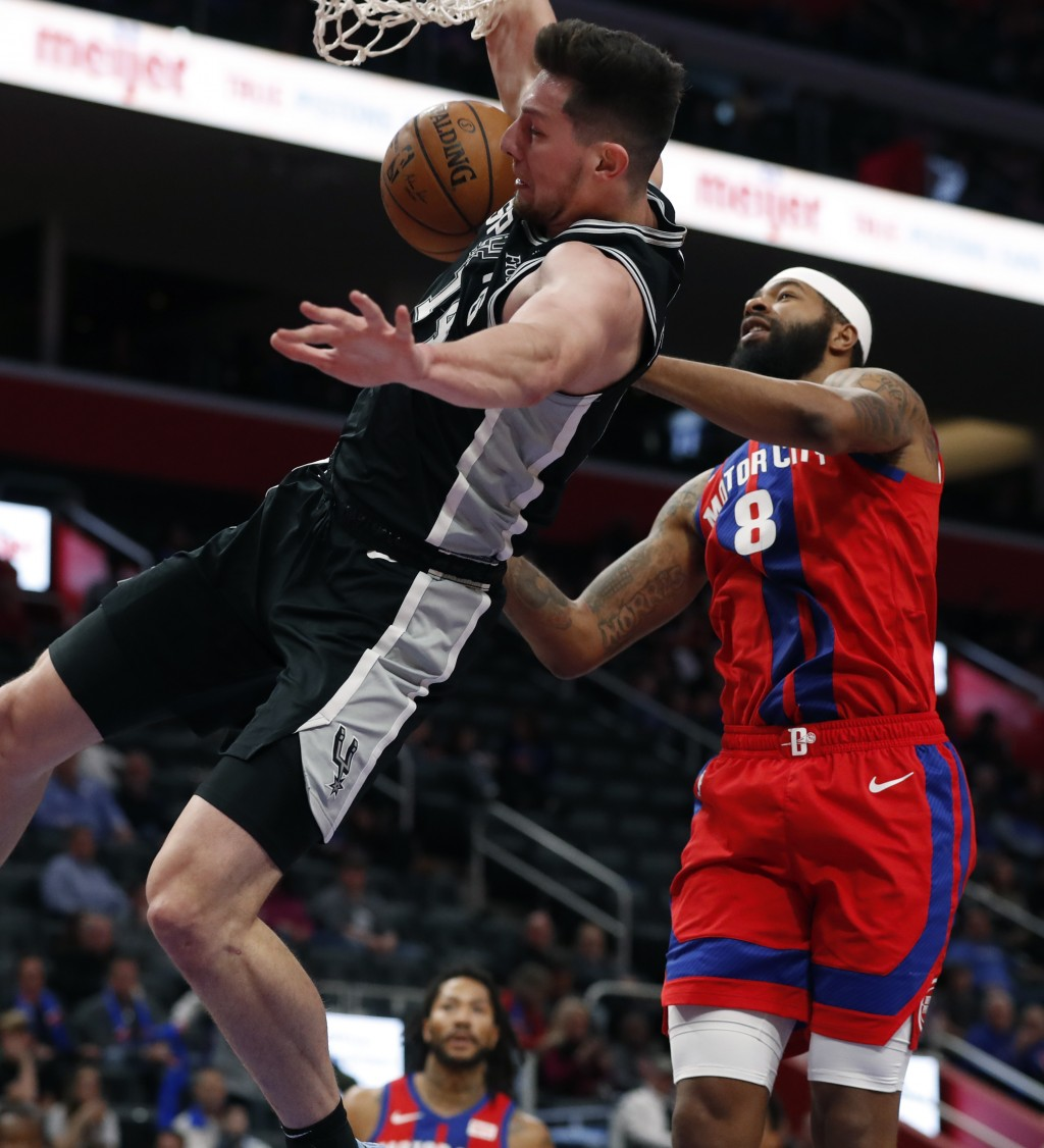 San Antonio Spurs forward Drew Eubanks (14) dunks on Detroit Pistons forward Markieff Morris (8) during the first half of an NBA basketball game, Sund...