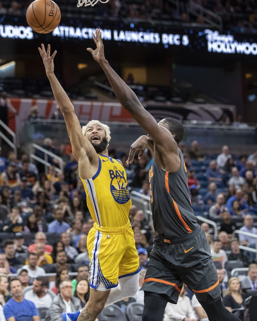 Golden State Warriors guard Ky Bowman (12) scores against Orlando Magic center Mo Bamba (5) during the first half of an NBA basketball game, Sunday, D...
