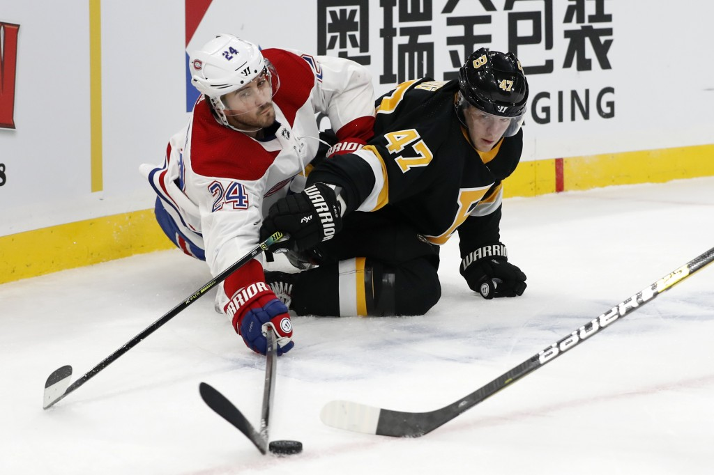 Montreal Canadiens' Phillip Danault, left, reaches to knock the puck away from Boston Bruins' Torey Krug (47) during the first period of an NHL hockey...