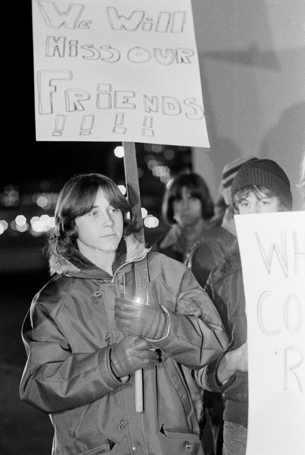 FILE - In this Dec. 4, 1979 file photo, a young man shields his candle from the wind during a memorial service for those killed during a stampede at a...