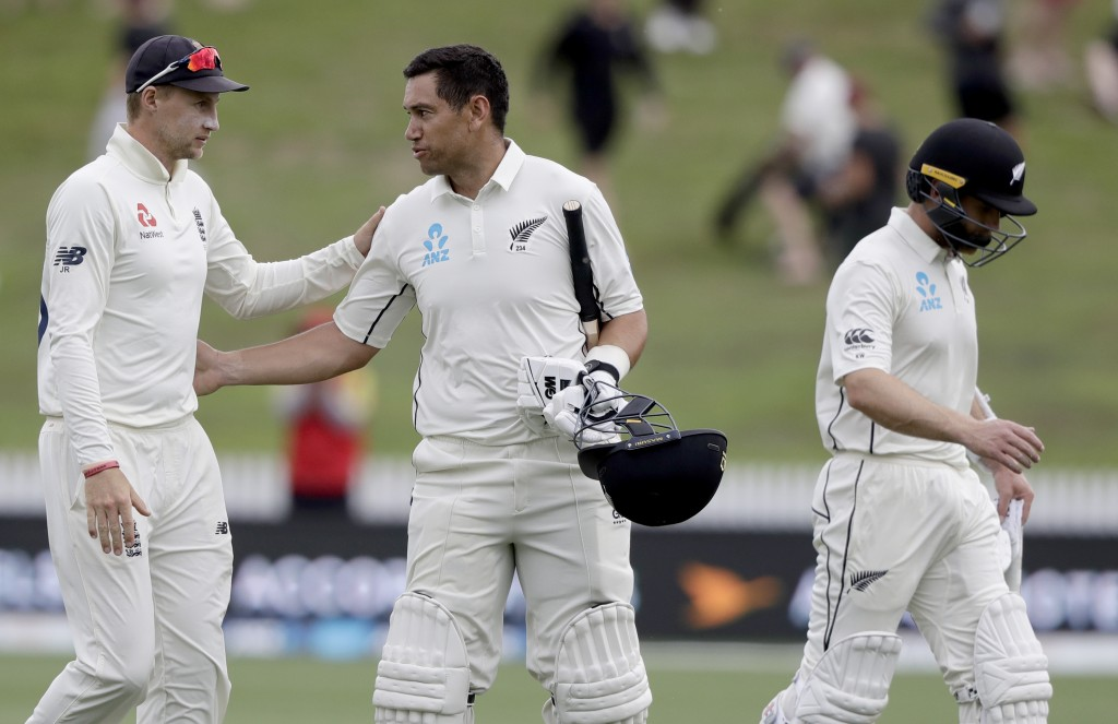 New Zealand's Ross Taylor, centre, congratulates England's Joe Root as they leave the field at the close of play on day four of the second cricket tes...