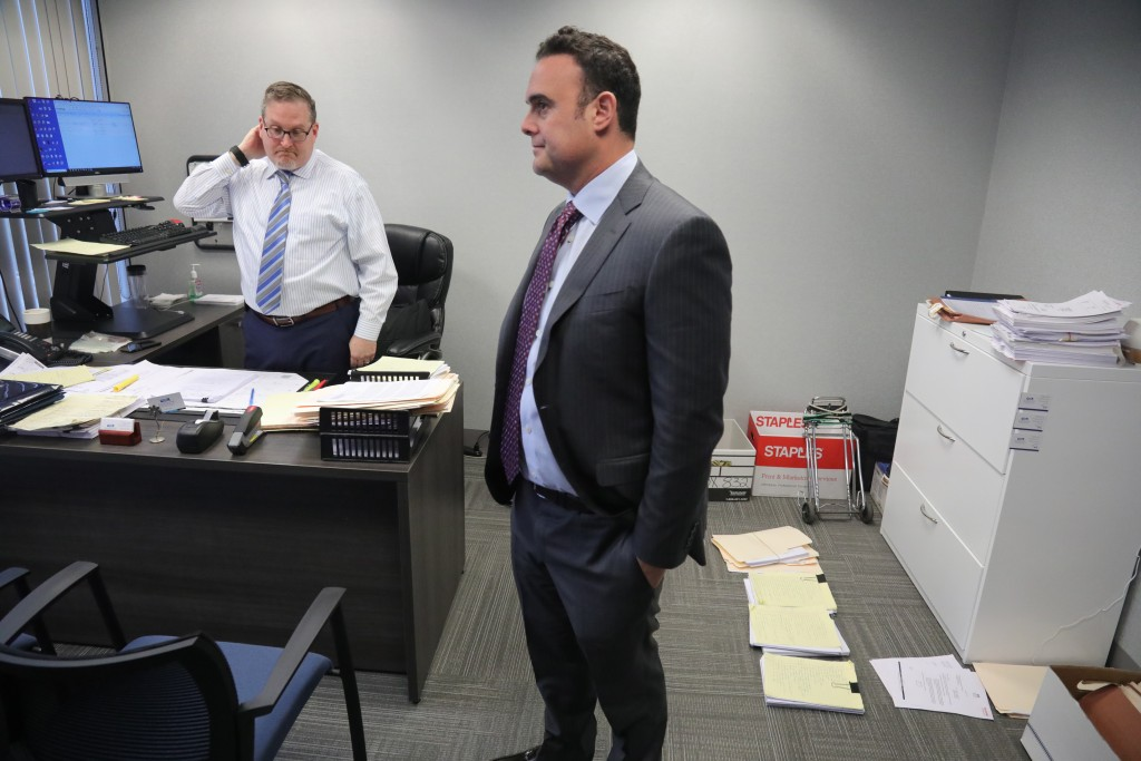 In this Tuesday, Oct. 29, 2019, photo, attorney Adam Slater, right, meets with his firm's managing attorney, Steven Alter, left, in Melville, N.Y. Sla...