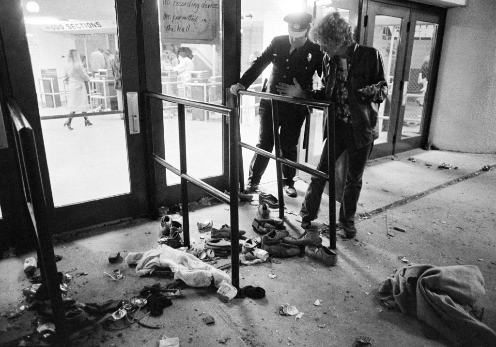 FILE - In this Dec. 3, 1979 file photo, a security guard and an unidentified man look at an area where several people were killed as they were caught ...