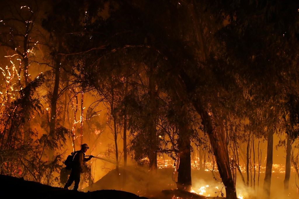 FILE - In this Oct. 31, 2019, file photo, a firefighter battles a wildfire known as the Maria Fire in Somis, Calif. A new technology being tested by C...