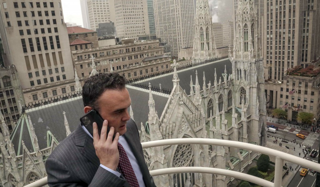In this Tuesday, Oct. 29, 2019, photo, attorney Adam Slater takes a phone call on a patio outside his high-rise Manhattan office overlooking St. Patri...