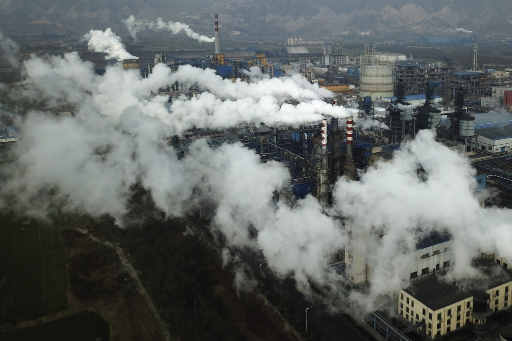 In this Nov. 28, 2019, photo, smoke and steam rise from a coal processing plant that produces carbon black, an ingredient in steel manufacturing, in H...