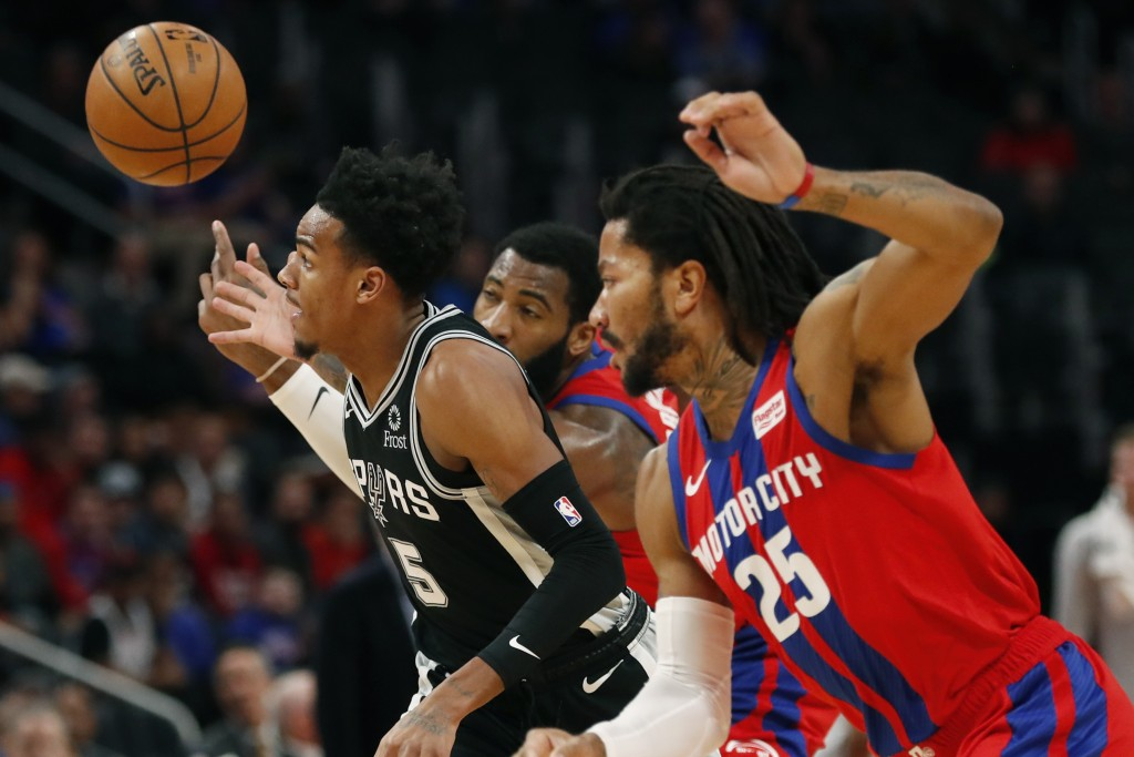 San Antonio Spurs guard Dejounte Murray (5), Detroit Pistons center Andre Drummond, rear, and guard Derrick Rose (25) reach for the loose ball during ...