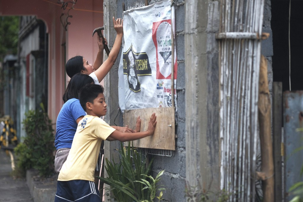 Residents reinforce their house as they prepare for a coming typhoon in Legazpi, Albay province, southeast of Manila, Philippines on Monday Dec. 2, 21...