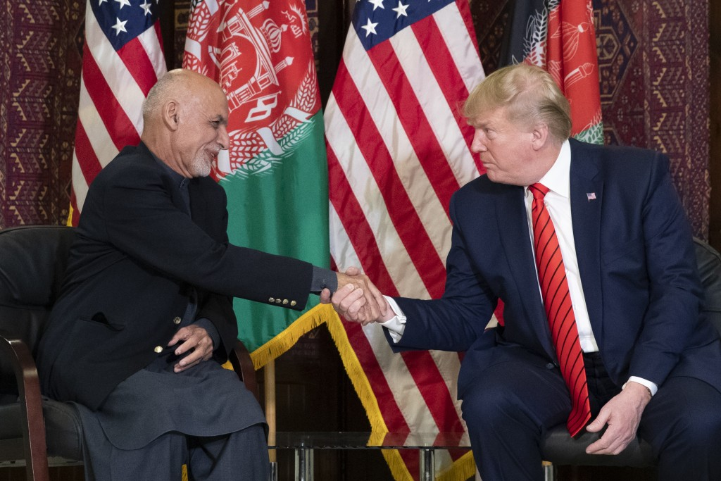 FILE - In this Thursday, Nov. 28, 2019 file photo, President Donald Trump shakes hands during a meeting with Afghan President Ashraf Ghani during a su...