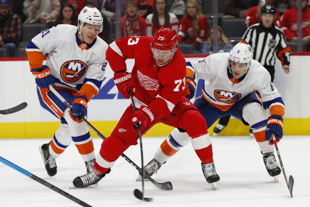 Detroit Red Wings left wing Adam Erne (73) skates past New York Islanders left wing Otto Koivula (21) and Ryan Pulock (6) in the second period of an N...