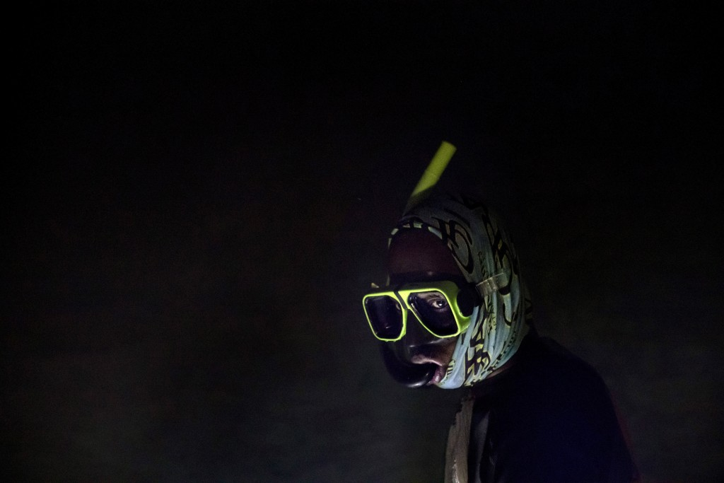 Nicholas Bingham enters the water to go night spearfishing, which is banned, especially in the sanctuaries set up to protect the island's endangered c...