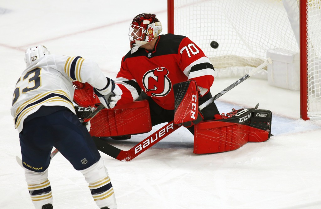 Buffalo Sabres forward Jeff Skinner (53) puts the puck past New Jersey Devils goalie Louis Domingue (70) during the first period of an NHL hockey game...