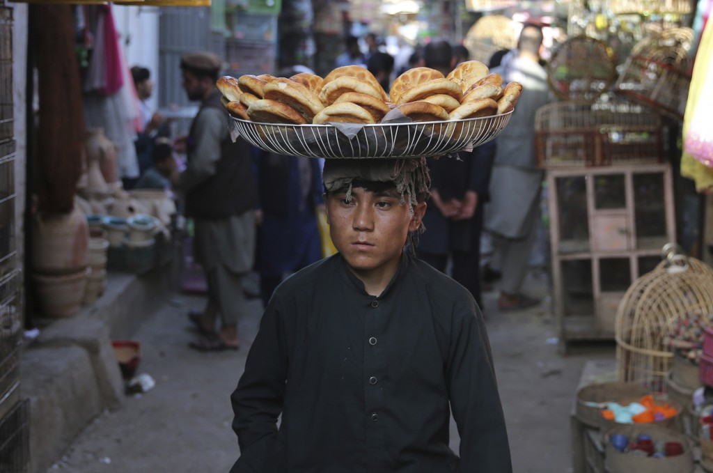 FILE - In this Aug 1, 2019 file photo, a boy carries bread for sale at a market in the old city of Kabul, Afghanistan. A new survey released by the As...