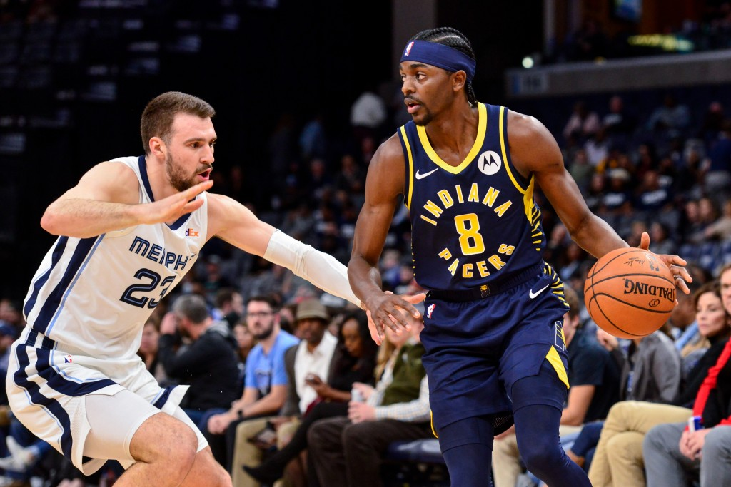 Indiana Pacers forward Justin Holiday (8) handles the ball against Memphis Grizzlies guard Marko Guduric (23) in the first half of an NBA basketball g...