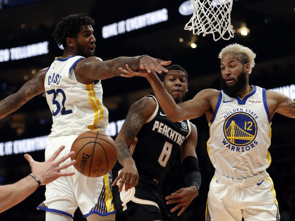 Atlanta Hawks guard Tyrone Wallace (8) passes the ball between Golden State Warriors forward Marquese Chriss (32) and guard Ky Bowman (12) in the firs...