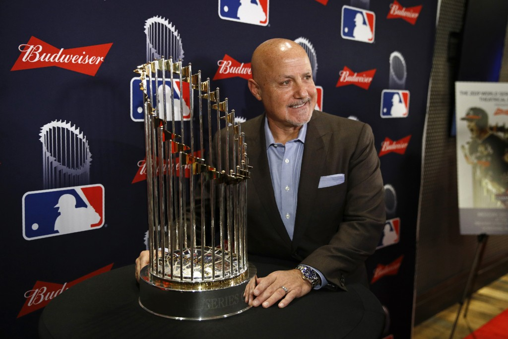 Washington Nationals general manager Mike Rizzo poses with the World Series trophy as he arrives for the premiere of a documentary film on the team's ...