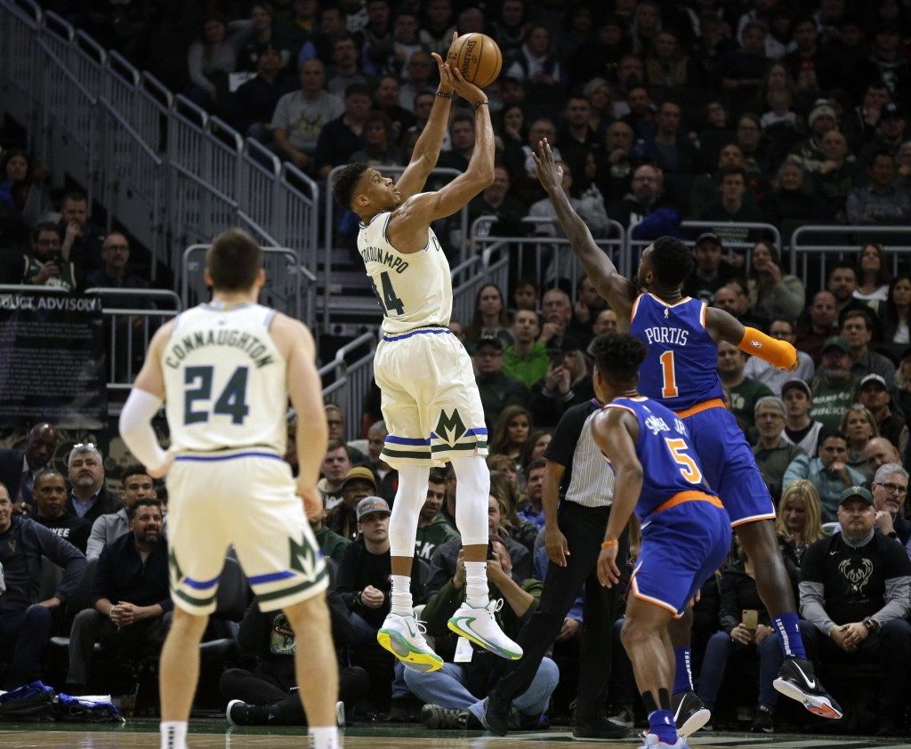 Milwaukee Bucks' Giannis Antetounmpo, center, shoots against the New York Knicks during the first half of an NBA basketball game Monday, Dec. 2, 2019,...