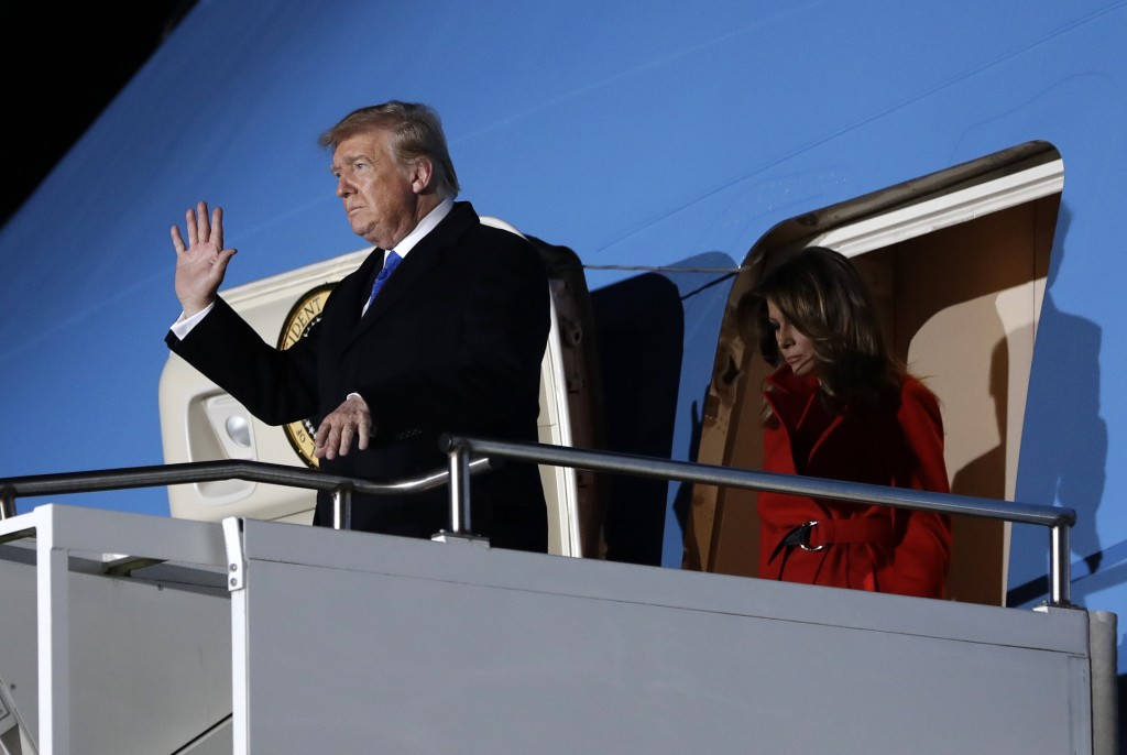 U.S. President Donald Trump waves as he and U.S. first lady Melania Trump arrive at Stansted Airport in England, Monday, Dec. 2, 2019. US President Do...