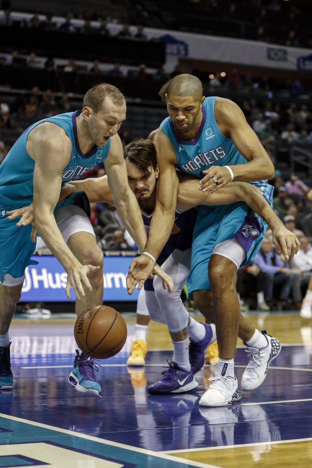 Phoenix Suns forward Dario Saric, center, battles Charlotte Hornets forward Cody Zeller, left, and guard Nicolas Batum (5) in the first half of an NBA...