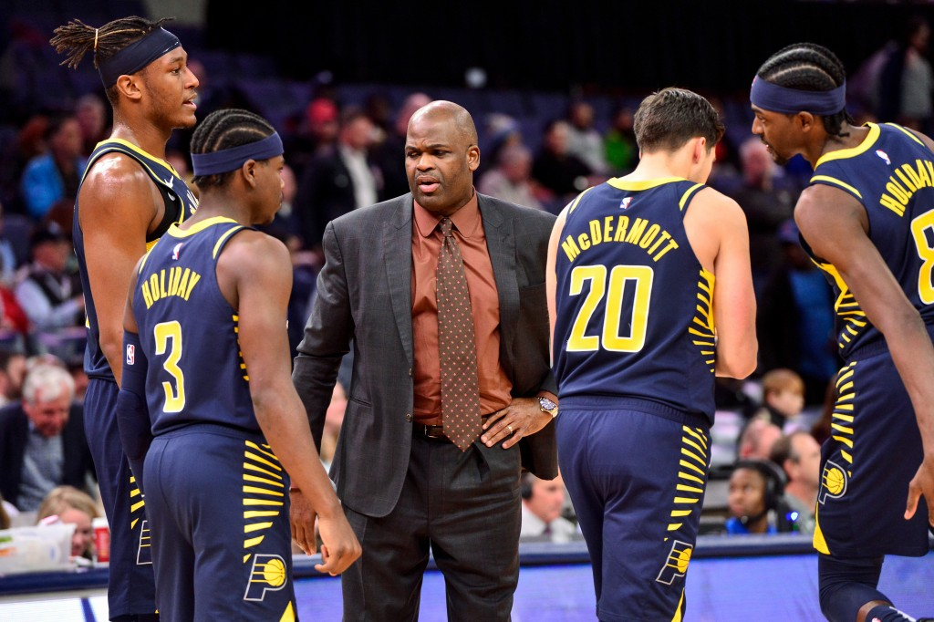 Indiana Pacers head coach Nate McMillan, center, talks with center Myles Turner (33), guard Aaron Holiday (3), and forwards Doug McDermott (20) and Ju...