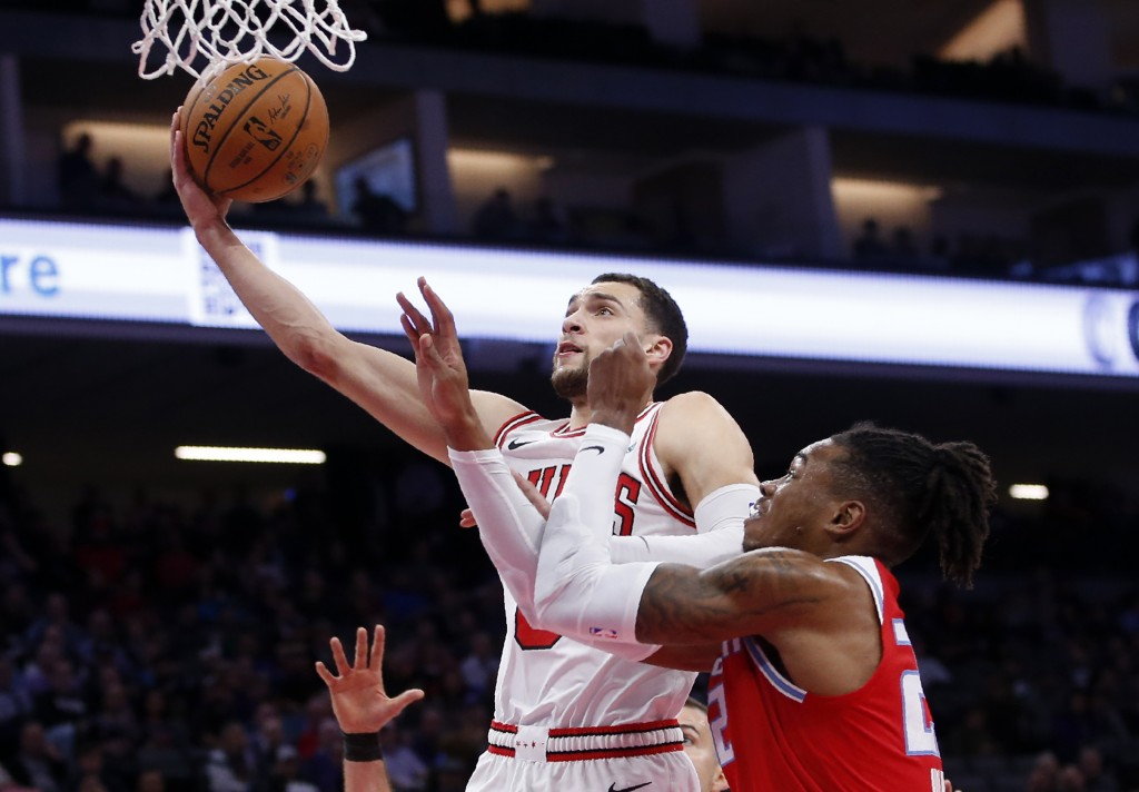 Chicago Bulls guard Zach LaVine, left, goes to the basket against Sacramento Kings forward Richaun Holmes, right, during the first quarter of an NBA b...