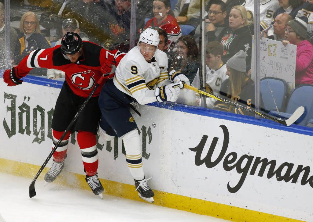Buffalo Sabres forward Jack Eichel (9) and New Jersey Devils defenseman Matt Tennyson (7) collide during the first period of an NHL hockey game Monday...